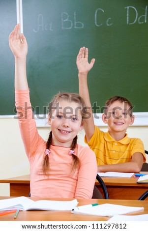 Portrait of lovely girl and her classmate on background raising hands at lesson - stock photo