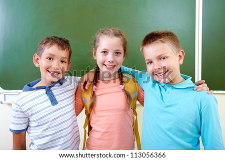 Portrait of lovely girl and two schoolboys looking at camera - stock photo
