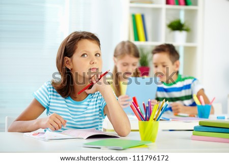 Portrait of lovely girl concentrating on drawing at workplace with schoolmates on background - stock photo