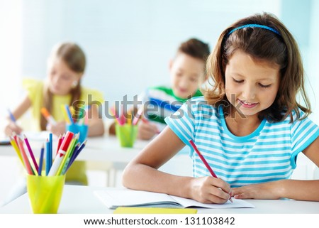 Portrait of lovely girl drawing at workplace with schoolmates on background - stock photo