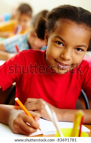 Portrait of lovely girl drawing with crayons at lesson - stock photo