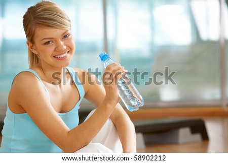 Portrait of lovely girl holding bottle of water in hand and smiling - stock photo