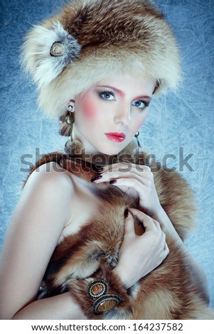 portrait of lovely girl in fur clothes against blue ice - stock photo