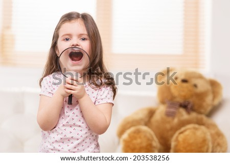 portrait of lovely girl playing with magnifying glass. small girl standing in bedroom and smiling - stock photo