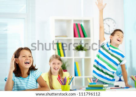 Portrait of lovely girl raising hand at workplace with happy classmates behind - stock photo