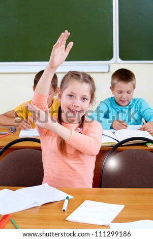 Portrait of lovely girl raising hand at workplace with schoolboys on background - stock photo