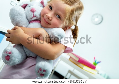 Portrait of lovely girl with her favourite soft toy - stock photo