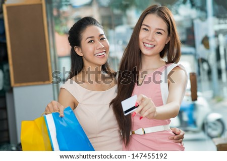 Portrait of lovely girlfriends giving a credit card while paying for her purchase