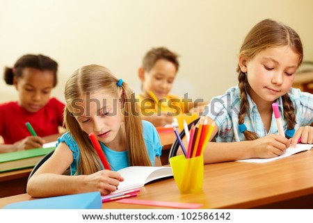 Portrait of lovely girls drawing with colorful pencils at lesson