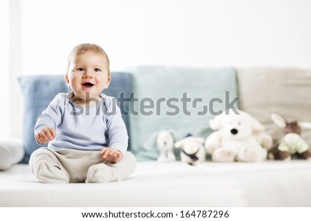 Portrait of lovely laughing baby boy with blue eyes and blue shirt sitting on couch and looking up, blurred toys in background. - stock photo