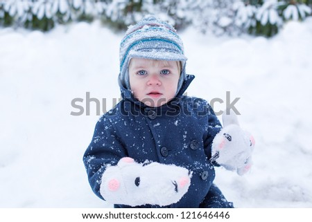 Portrait of lovely little toddler boy  on beautiful winter snowy day - stock photo