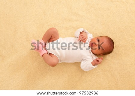 portrait of lovely newborn lying on the back top-up view - stock photo