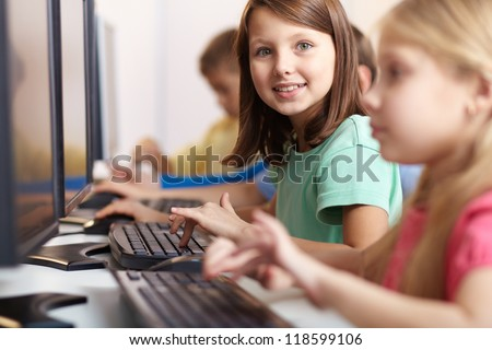 Portrait of lovely schoolgirl looking at camera while typing at lesson - stock photo