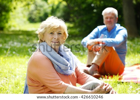 Portrait of lovely senior couple relaxing outdoor. Elderly woman looking at camera and sitting on grass while old man sitting at background.
