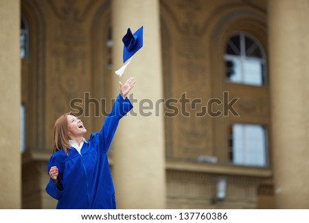 Portrait of lovely student throwing graduation hat - stock photo