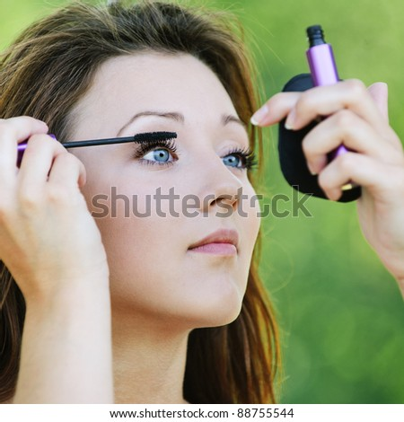 Portrait of lovely teenage girl colouring her lashes and looking in mirror at summer green park.