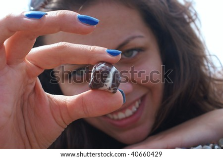 portrait of lovely woman showing stone (stone in focus) . - stock photo