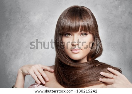 Portrait of lovely woman with long  hair on gray background - stock photo