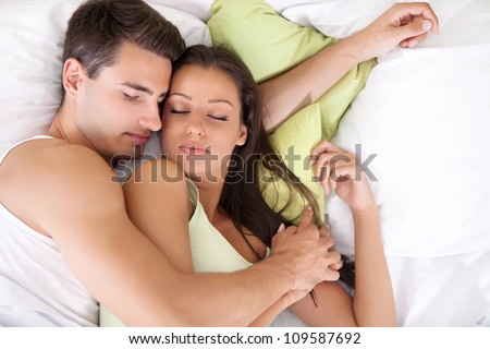 Portrait of lovely young couple sleeping together on bed - stock photo