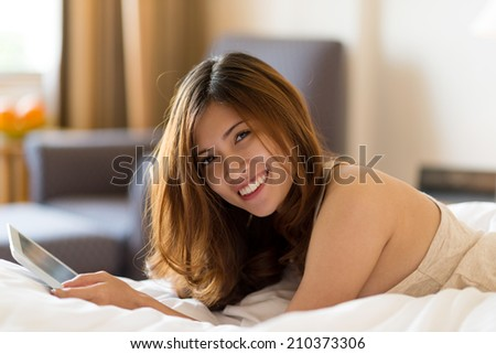 Portrait of lovely young woman with a digital tablet lying in her bed - stock photo