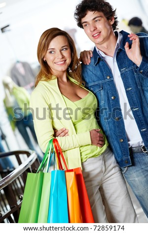 Portrait of loving couple choosing something in trade center and smiling - stock photo