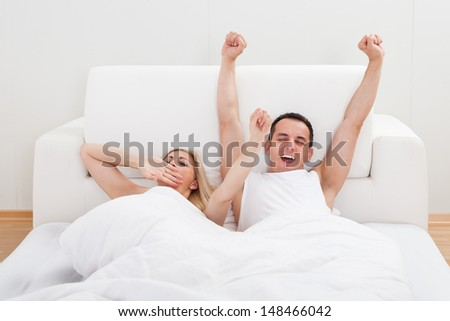 Portrait Of Loving Couple Waking Up In Bed - stock photo