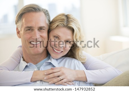 Portrait of loving mature woman embracing man from behind at home - stock photo