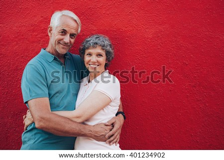 Portrait of loving middle aged man and woman standing together against red background. Senior couple embracing against red wall with copy space. - stock photo