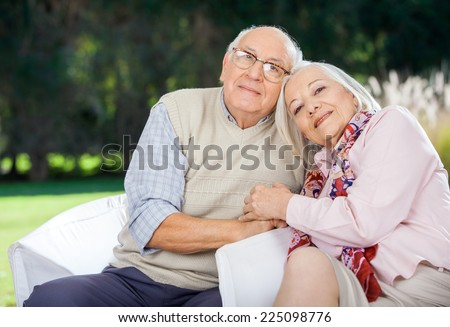 Portrait of loving senior couple sitting on chairs at nursing home porch - stock photo