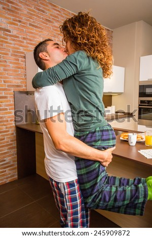 Portrait of loving young couple in a passionate kiss while having breakfast on the home kitchen - stock photo