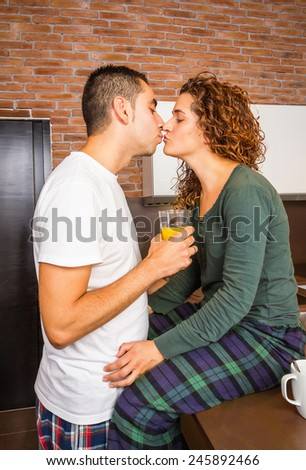 Portrait of loving young couple kissing while having breakfast on the home kitchen - stock photo