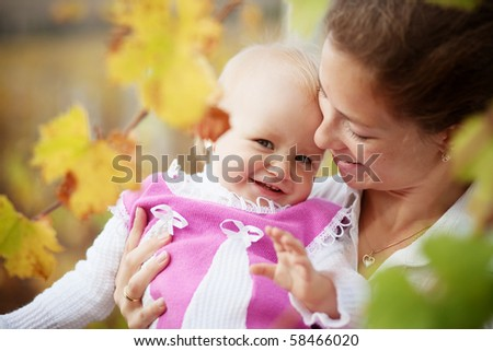 Portrait of loving young mother holding her baby in autumn park