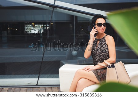 Portrait of luxury woman having mobile phone conversation while sitting in modern urban place, attractive confident female talking on her cellphone while sitting near skyscraper building in summer day - stock photo