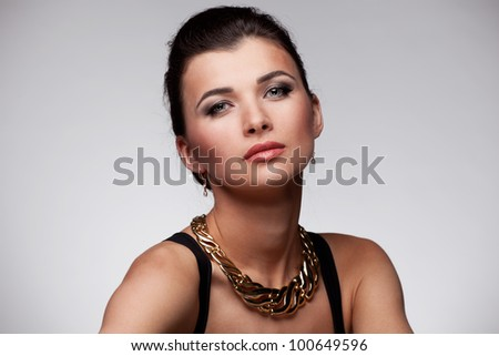 Portrait of luxury woman in exclusive jewelry and  black dress on natural background - stock photo