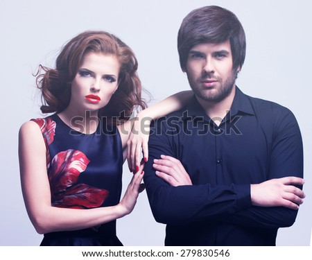 Portrait of luxury young couple in love posing at studio dressed in classic clothes.