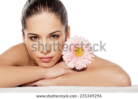 Portrait of lying beautiful young woman with gerbera - stock photo