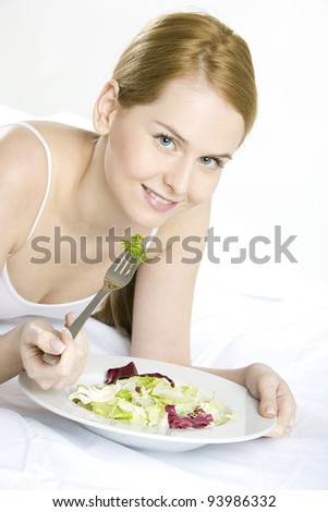 portrait of lying down woman eating salad - stock photo