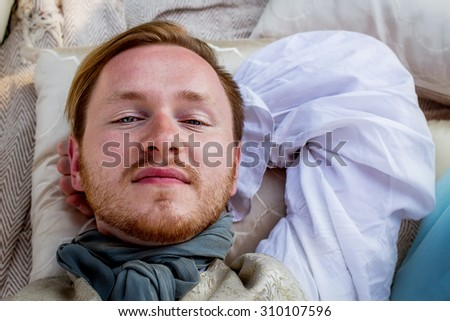 Portrait of lying handsome ginger hair man dressed in regency period costume. Image with selective focus - stock photo