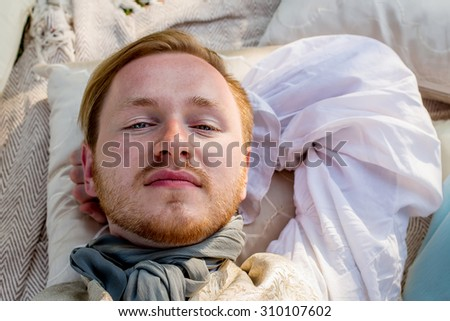 Portrait of lying handsome ginger hair man dressed in regency period costume with sun beam on his face. Image with selective focus - stock photo