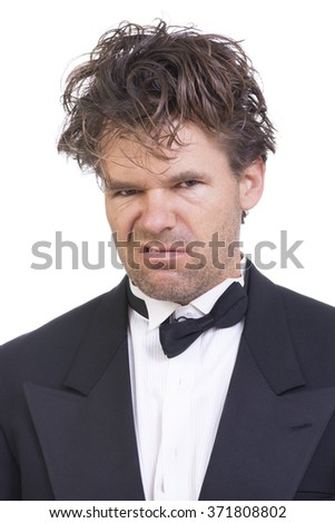 Portrait of mad deranged Caucasian man with long messy hair wearing messed up black tuxedo on white background - stock photo