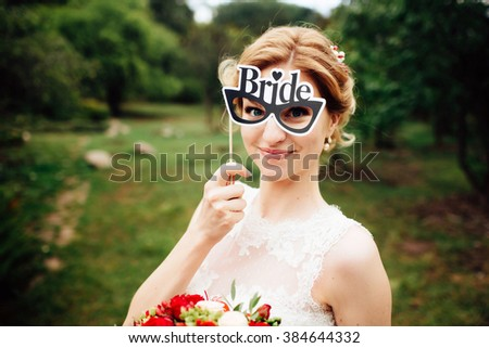 Portrait of magical beautiful young blonde bride in elegant dress with funny glasses - plate labeled bride in the park. Close up photo - stock photo
