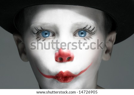 portrait of make up clown boy with red nose