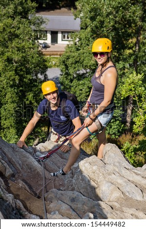 Portrait of male and female climbers with safety equipment relaxing on rock - stock photo