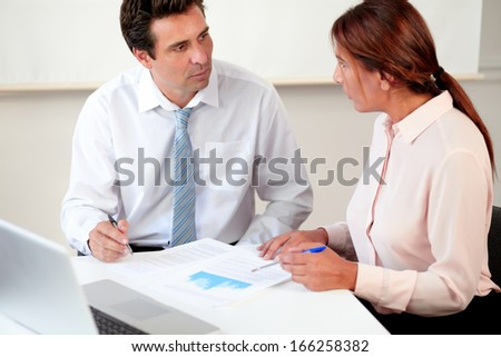 Portrait of male and female enterpreneur working on documents while sitting on office desk