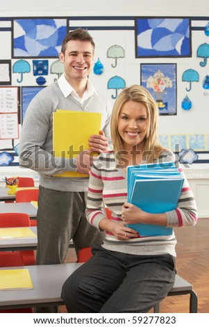 Portrait Of Male And Female Teacher Sitting At Desk In Classroom