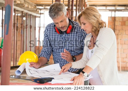 Portrait Of Male Architect And Mature Woman Discussing Plan On Blueprint At Construction Site - stock photo