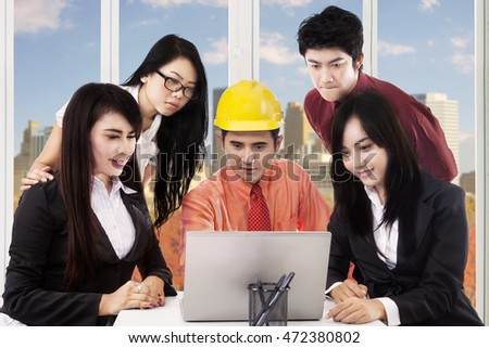 Portrait of male architect wearing helmet and discussing with his partners in the office while looking at the laptop together
