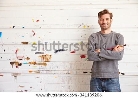 Portrait Of Male Artist Leaning Against Paint Covered Wall - stock photo