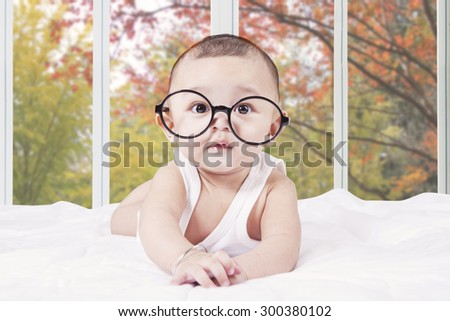 Portrait of male baby looking at the camera while lying on bedroom and wearing a round glasses - stock photo