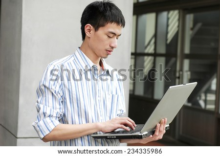 portrait of male college student use laptop at campus - stock photo
